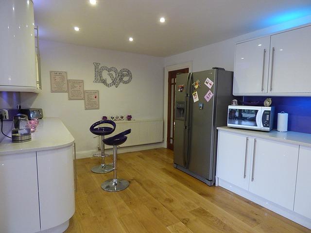 bílá kuchyně, modré stoličky, lednice, mikrovlnka