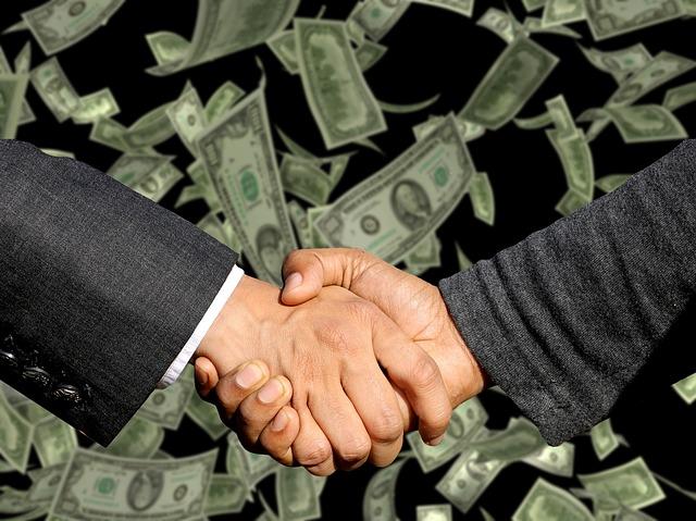 podání rukou a bankovky v pozadí